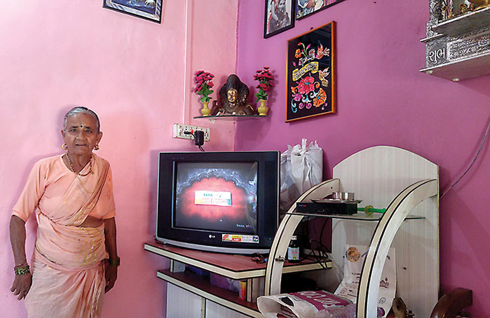 A woman happily poses with her television set