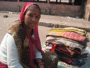 Jamna selling old clothes in a mandi near Raghubir Nagar