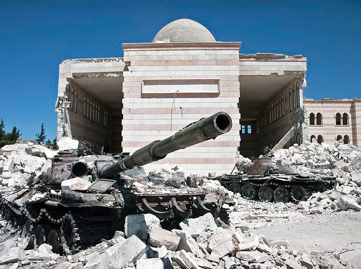 Two destroyed tanks in front of a mosque in Syria in 2012
