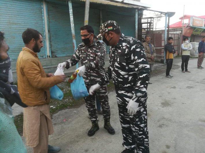 CRPF men distributing essential items in Baramulla of Kashmir earlier this week. (Photo @PIB_India)