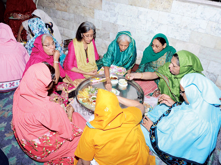Dawoodi Bohra women eating around a traditional 'thaal'.