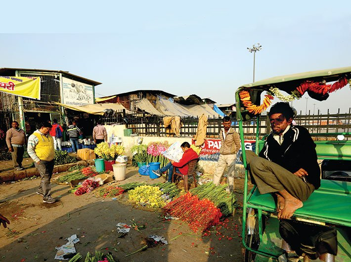 With no customers around,  a vendor and a rickshaw puller bide their time at the  Ghazipur flower mandi