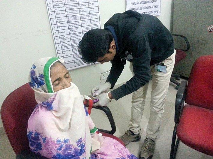 DNP+ member at an ART centre attending to an HIV patient
