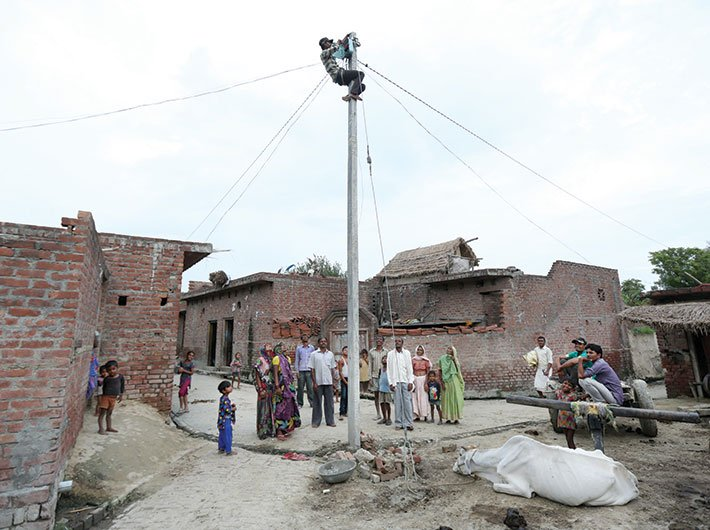 An electricity pole being set up at a village in Uttar Pradesh's Badaun district