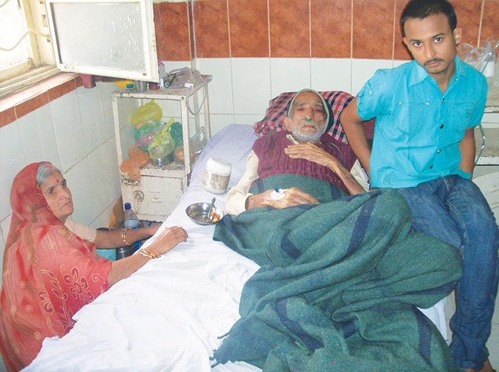 Pradeep Gehlot and his mother with his ailing father Srikrishna. Photo courtesy: Swasthya Adhikar Manch