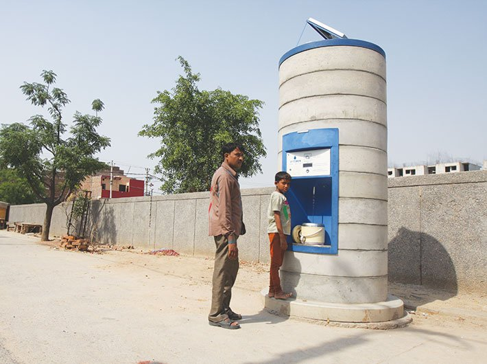 Ravi Kumar and his son drawing water from the Sarvajal ATM at Savda Ghevra