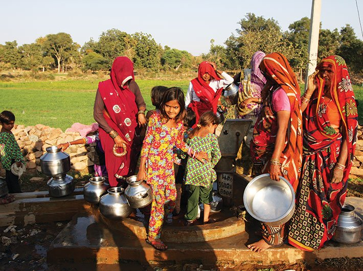 Women and children wait for their turn to fill water from a hand-pump in Bundelkhand
