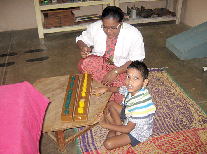 Kabila Devi, a qualified physiotherapist, gives therapy to a child
