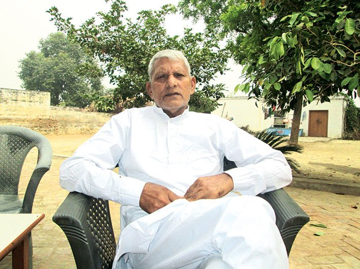 Hariraj Tyagi, village head, Talheta, sitting in his home.